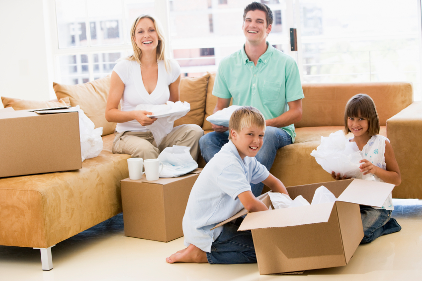 Family unpacking boxes in new home smiling